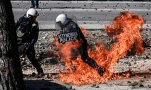 Greek riot police run away from a firebomb
