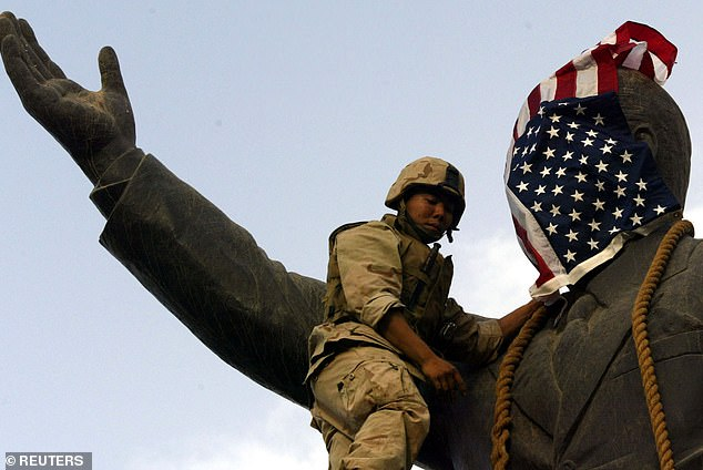 A US Marine covers the face of a statue of Iraqi President Saddam Hussein with a American flag in Baghdad on 9 April, 2003. Dr Cunliffe told MailOnline that ISIS would not have existed were it not for the coalition's invasion of Iraq to topple Saddam in 2003
