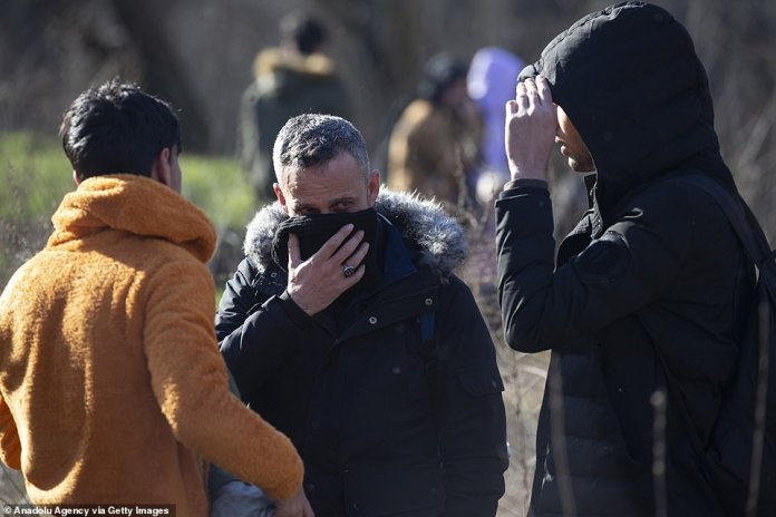 Men cover their faces in an attempt to protect themselves against tear gas after Greek border guards used it to dispel crowds that were gathered at the border