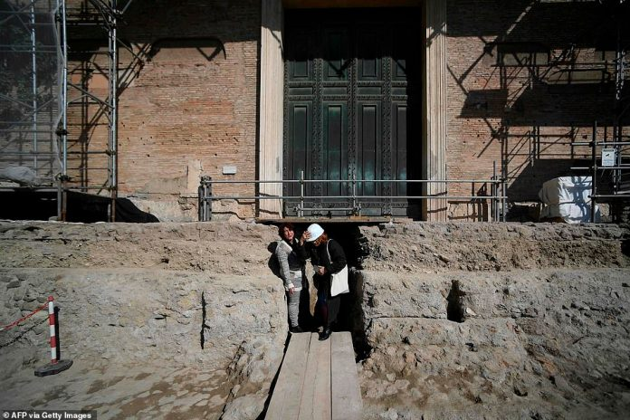 People stand by the access to an ancient tomb thought to belong to Rome's founder Romulus, who is believed to have killed his brother before founding Rome