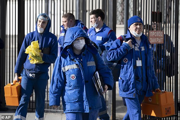 Russian medical workers are pictured walking after carrying out health checks on a group of passengers who had arrivedat Kievsky rail station in Moscow with a suspected coronavirus carrier on February 21