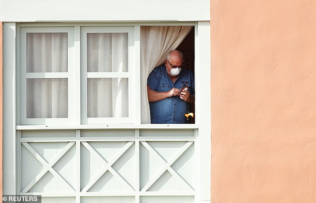 A guest wearing a protective face mask stands at the window of the H10 Costa Adeje Palace today where tourists were told they face two weeks in quarantine