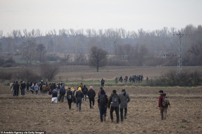 Refugees making their way across a field towards Europe via Turkey on Friday