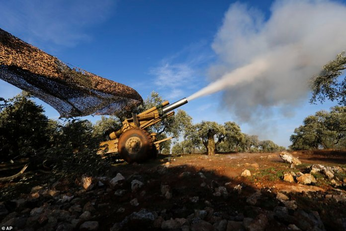 Turkish backed rebel fighters fire a howitzer toward Syrian government's forces positions near the village of Neirab in Idlib province