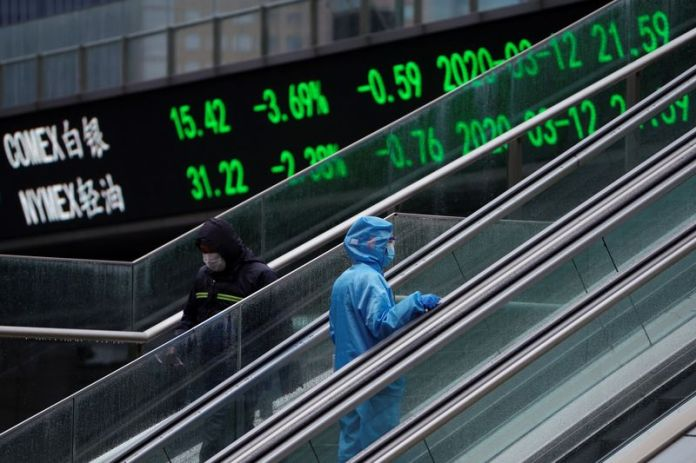 © Reuters. FILE PHOTO: Pedestrian in protective suit rides an escalator near an overpass with an electronic board showing stock information in Shanghai