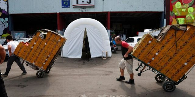 Workers pull dollies loaded with boxes of produce past a decontamination tent at the Centro de Abastos, the main food distribution center in Mexico City, Tuesday, April 7, 2020.
