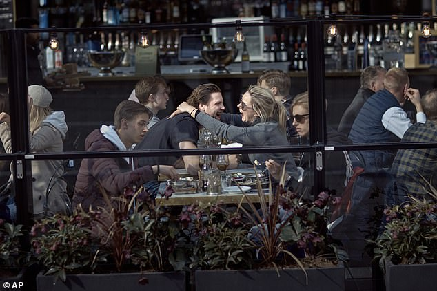 Bars have remained open in Sweden (pictured, a venue in Stockholm on Saturday) meaning citizens have been free to socialise as normal despite the pandemic