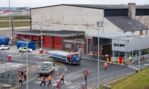 Workers outside a hangar at Birmingham airport, which is being converted into a large morgue.