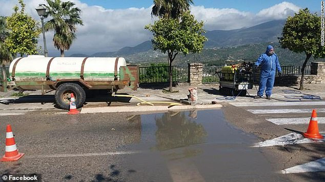 Each vehicle that enters the town's one remaining access point must drive through a make-shift ditch to ensure their tyres are disinfected. Two men wearing protective clothing wash every vehicle with bleach and water