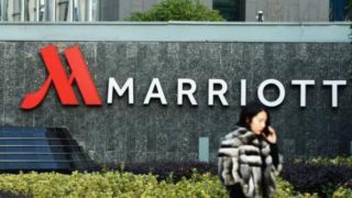 a woman walking past Marriott signage in Hangzhou in China's Zhejiang province.