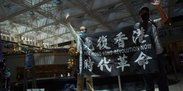 """Protesters gesture with five fingers, signifying the """"Five demands - not one less"""" in a shopping mall during a protest against China's national security legislation for the city, in Hong Kong, Monday, June 1, 2020."""
