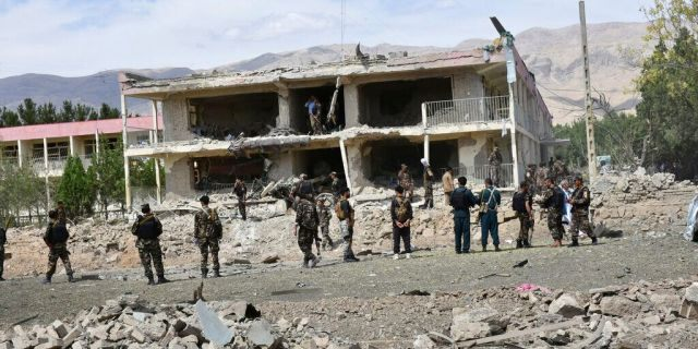 Afghan security personnel inspect the site of a car bomb blast on an intelligence compound in Aybak, the capital of the Samangan province in northern Afghanistan, July 13. Taliban insurgents launched a complex attack on the compound that began with a suicide bombing, officials said. (AP Photo)