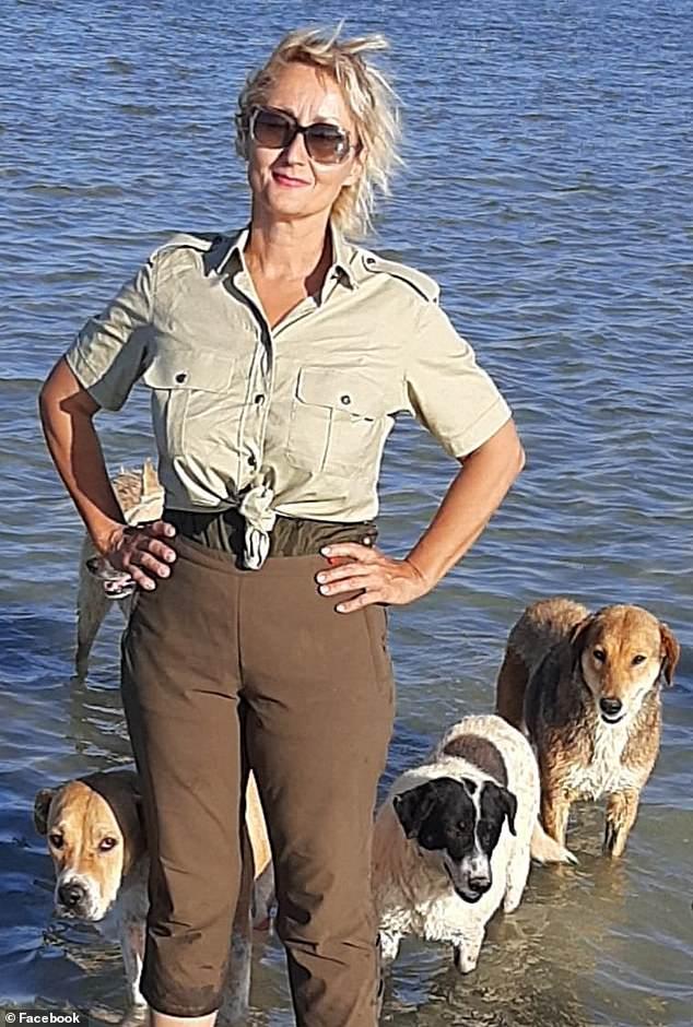 Tiziana is pictured in the sea near her beach-side shelter with three of her rescue dogs before the massacre
