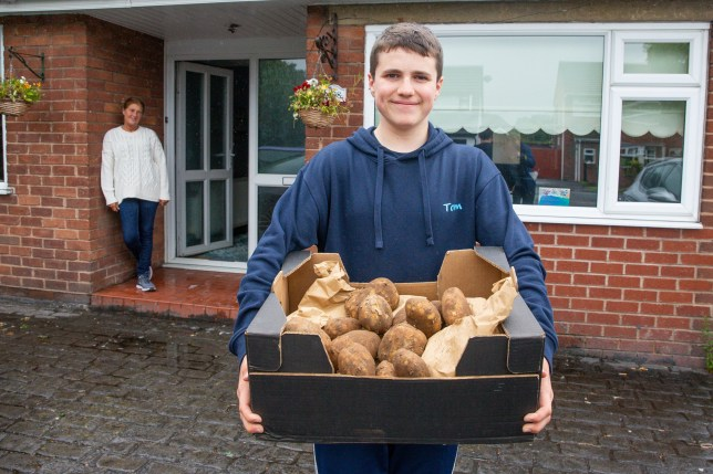 Thomas Brennan,16, on a delivery with a box of potatoes.