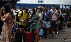 People wearing face masks to prevent the spread of coronavirus wait to board a ferry in the port of Piraeus, near Athens, on Friday, 7 August 2020.