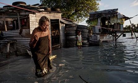 An elderly woman wades through knee-high sea water that has flooded her house in Eita settlement, Tarawa, Kiribati.