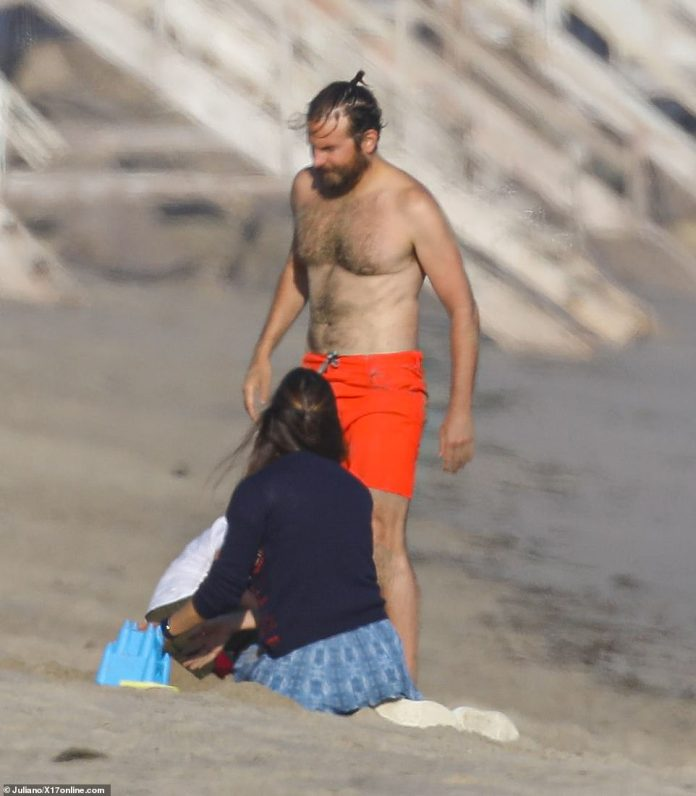 Pecs appeal: Bradley displayed his muscular physique while enjoying a beach playdate with Jen