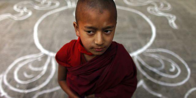 "A Tibetan monk stands at a Tibetan Monastery during the third day of ""Losar,"" or Tibetan New Year, at Baudhanath Stupa in Katmandu, Nepal, Friday, Feb. 24, 2012."