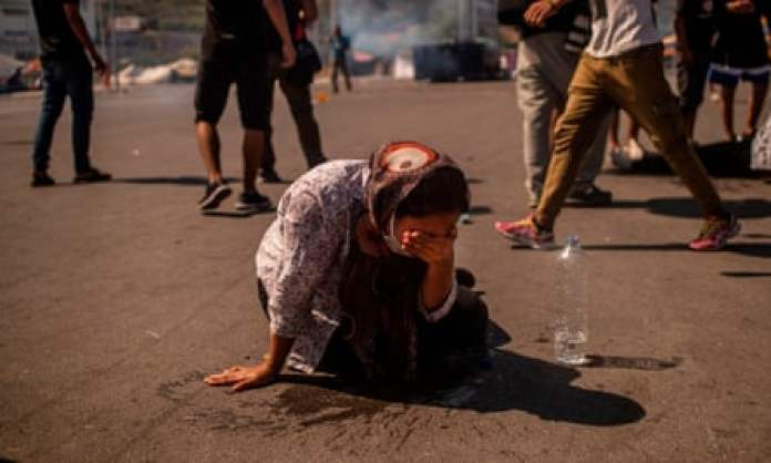 A woman cleans her eyes with water after police threw tear gas during clashes near the city Mytilene on the Greek island of Lesbos on 12 September.
