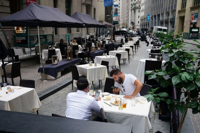 © Reuters. FILE PHOTO: People eat at a mostly empty restaurant with tables on the street in the financial district