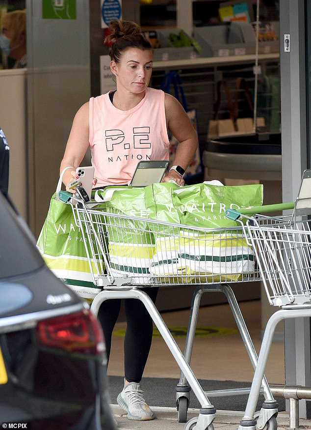 Busy: The WAG appeared in good spirits as she left the shop laden with bags and headed back to the car