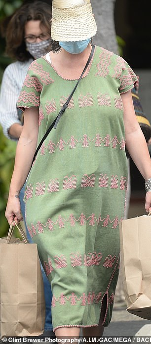 Loading up: She was seen exiting the high end boutique with two paper shopping bags that were packed to the brim with clothing items and various goods