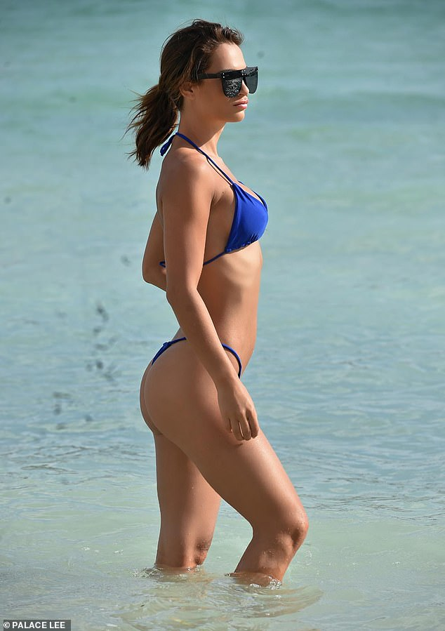 Sizzling: The sexy blue two-piece offered a glimpse of Nicole's peachy posterior as she strolled through the waves