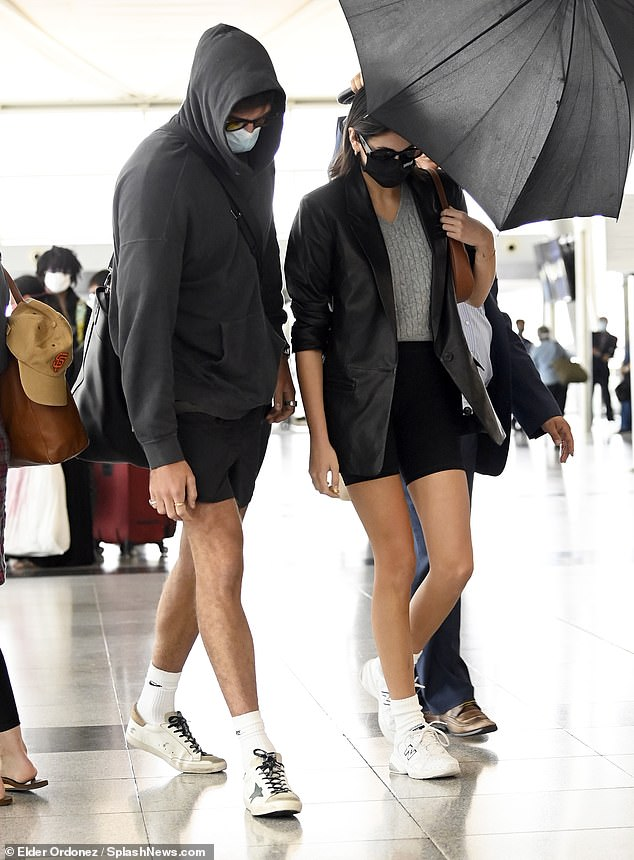 Low-profile: The Australian actor and daughter of Cindy Crawford appeared to be keeping a low-profile, as he pulled up the hood of his sweatshirt and she ducked her head under an umbrella