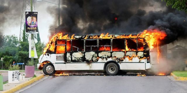 "A burning bus, set alight by cartel gunmen to block a road, is pictured during clashes with federal forces following the detention of Ovidio Guzman, son of drug kingpin Joaquin ""El Chapo"" Guzman, in Culiacan, Sinaloa state, Mexico Oct. 17, 2019. (REUTERS/Jesus Bustamante)"