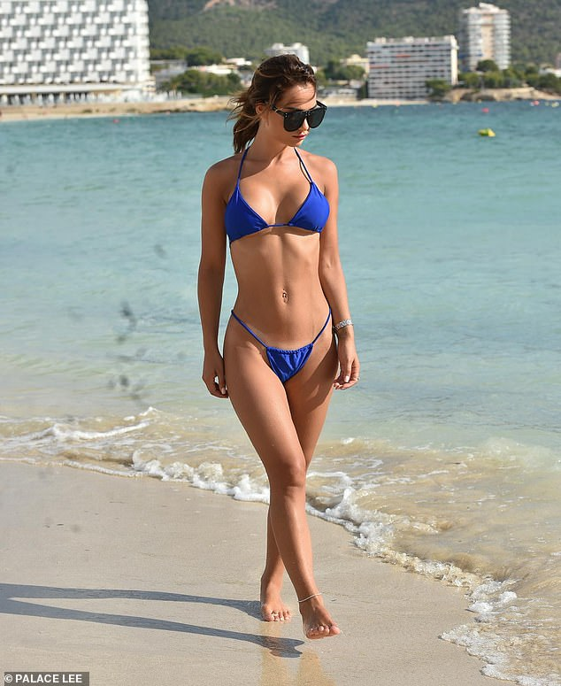 Confident: Nicole showed off her tanned figure in the plunging blue two-piece as she took a stroll along the beach
