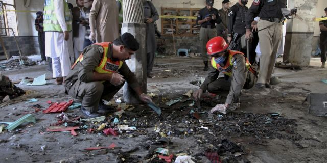 Rescue workers and police officers examine the site of a bomb explosion in an Islamic seminary in Peshawar, Pakistan, Tuesday, Oct. 27, 2020. (AP Photo/Muhammad Sajjad)
