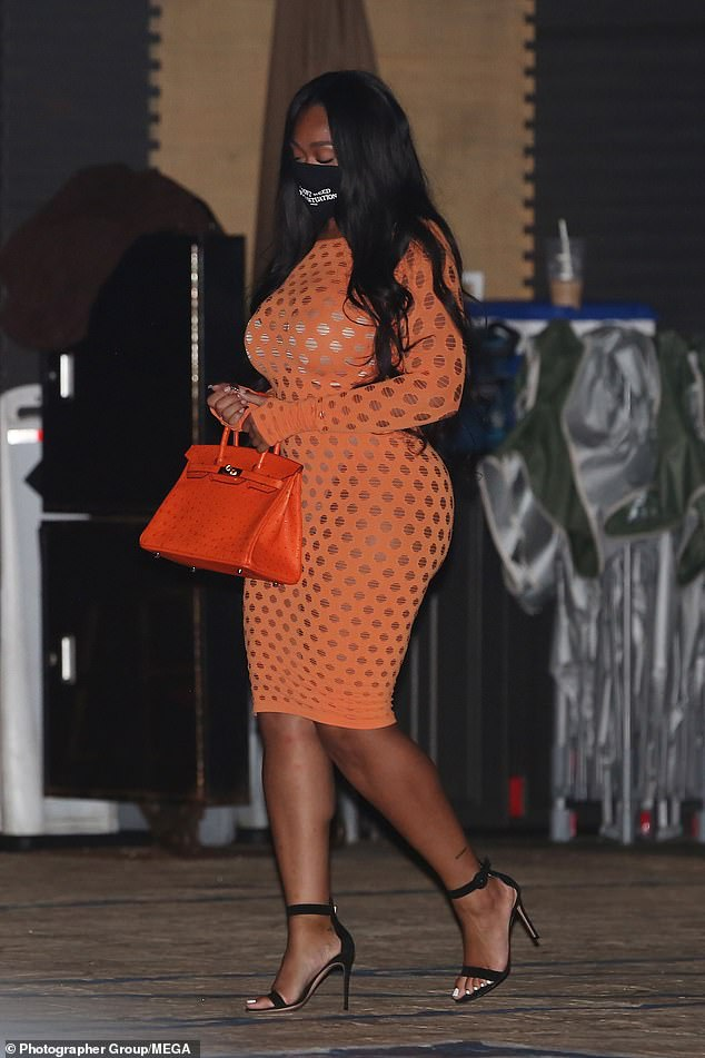 Beaming beauty: Jordyn Woods poured her curves into an orange mesh dress while dining at the trendy Nobu Malibu with her basketball player beau