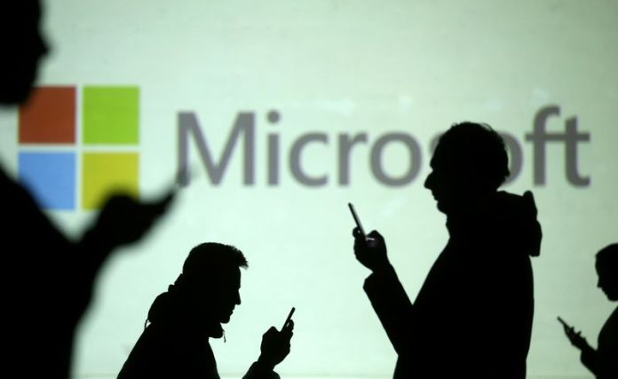 © Reuters. Silhouettes of mobile users are seen next to a screen projection of Microsoft logo in this picture illustration