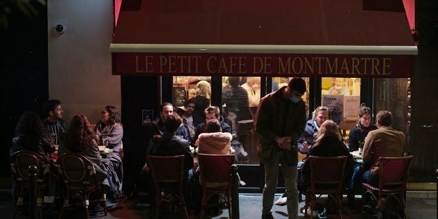 In this Sept. 26, 2020 file photo, people enjoy a drink in a cafe terrace in Paris. French authorities have placed the Paris region on maximum virus alert on Monday, banning festive gatherings and requiring all bars to close but allowing restaurants to remain open, as numbers of infections are rapidly increasing. (AP Photo/Lewis Joly, File)
