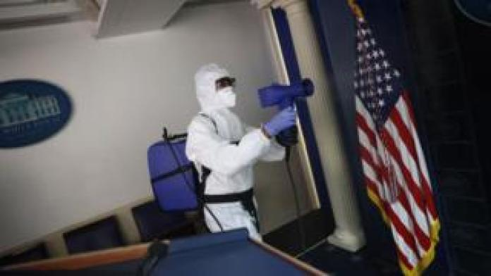 Workers in hazmat suits were seen sanitising eh White House briefing room on Monday