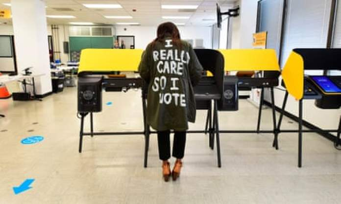 """Tonya Swain votes in Norwalk, California, while wearing a coat that mimics one worn by Melania Trump in 2018 which read, """"I really don't care. Do u?"""""""