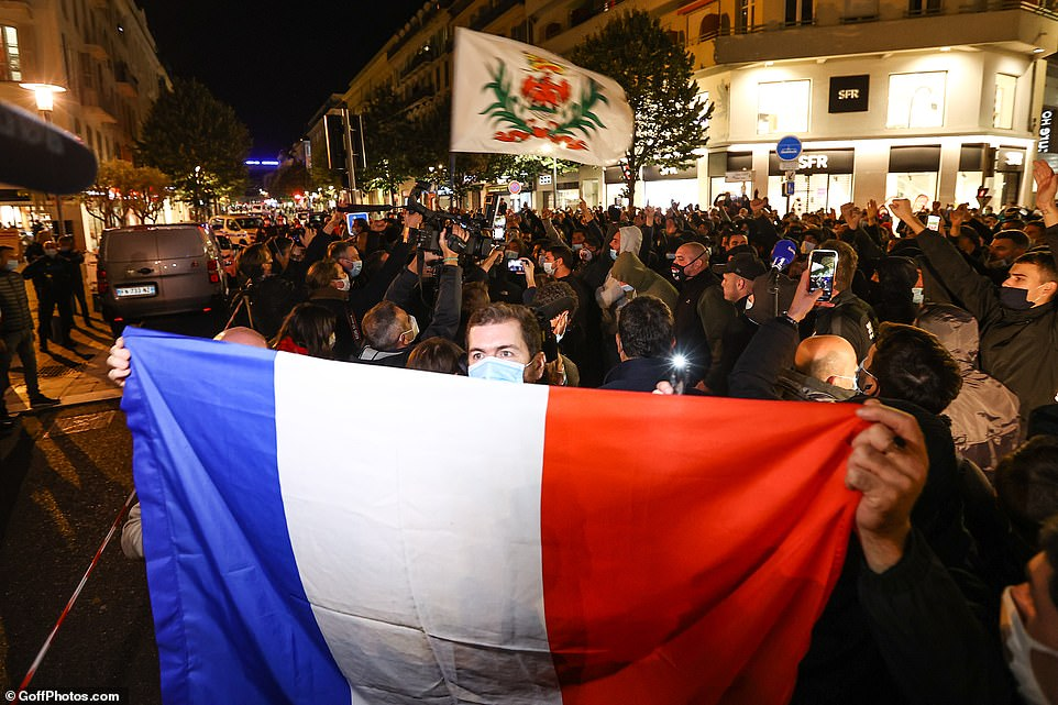 Tribute to the victims of the attack on the Notre-Dame basilica in Nice, with mourners holding the tricolor flag by the church