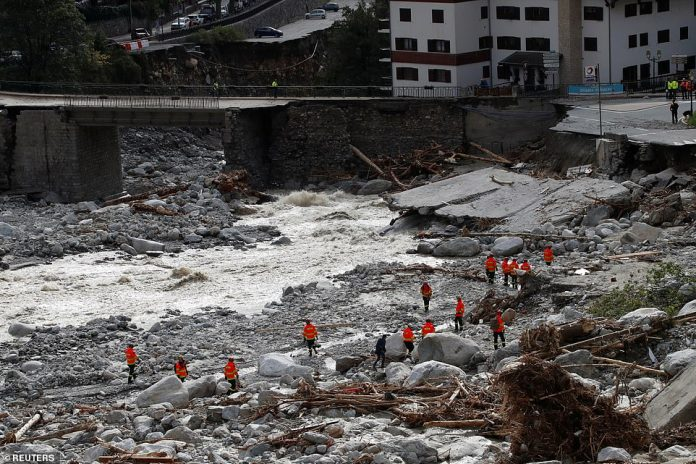 Firefighters and rescue workers examine an area to the east of Saint-Martin-Vestubie, where roads and fields were swept away by a torrent of floodwater as it raced downhill