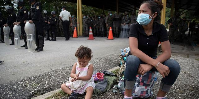An Honduran migrant and her daughter sit at a roadblock set by security forces in Poptun, Guatemala, Friday, Oct. 2, 2020. (Associated Press)