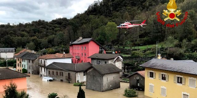 In this image made available Sunday, Oct. 4, 2020, a firefighters' helicopter flies over flooding in the town of Ornavasso, in the northern Italian region of Piedmont.