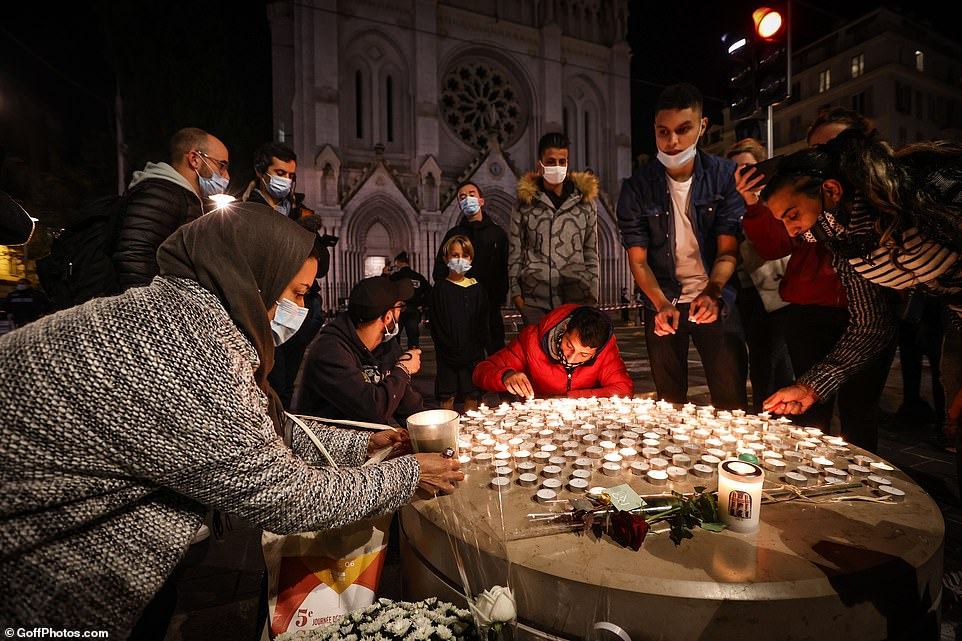 People light candles outside the Notre-Dame de l'Assomption Basilica in Nice in a vigil to remember the victims