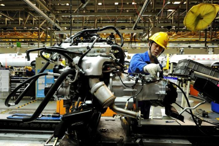 An employee works on a car in China