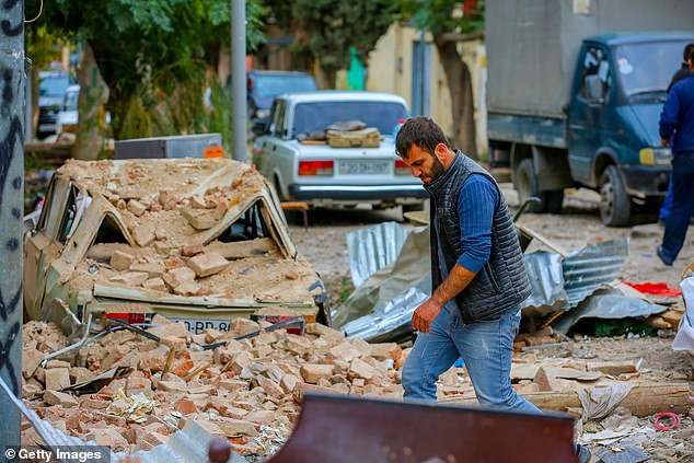 A man walks among debris from damaged buildings from recent shelling during a military conflict over the breakaway region of Nagorno-Karabakh, in the city of Ganja, Azerbaijan