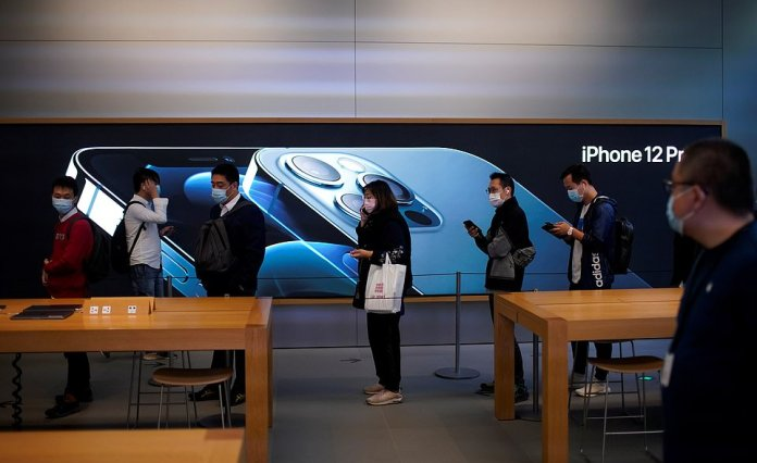 Customers look bored as they wait for the new iPhone in Sydney. There were fewer people lining up outside than last year for the iPhone 11