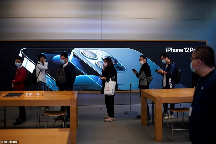 People line up as they wait inside the in Shanghai Apple Store. Apple's 5G new iPhone 12 and 12 Pro are preceded by the sale of iPhone 12 Max and Mini next month
