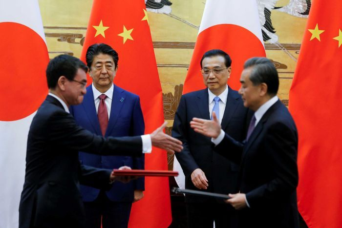 Leaders of China and Japan shake hands while in front of large flags of their respective nations