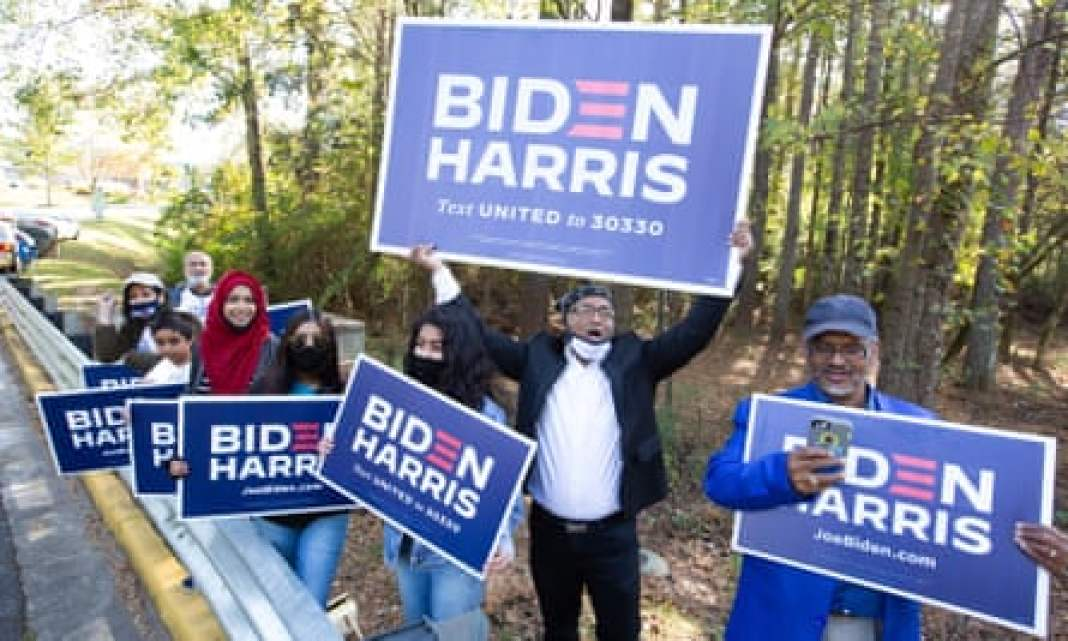 Gwinnett county voters including Menar Hague, centre, wave Biden-Harris campaign signs at the entrance to Lucky Shoals Park polling station in Norcross, Georgia.