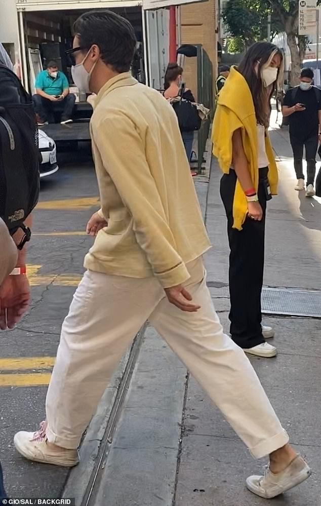 Hippy chic: The 26-year-old donned a muted yellow button-down shirt with white linen pants cuffed at the ankle, over a pair of dirty white sneakers
