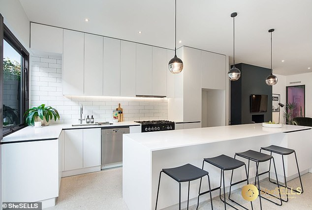 White on the mark: The home's kitchen has white tiling and cabinetry with modern touches