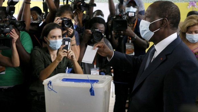 Ivory Coast President Alassane Ouattara (R) casts his vote at a polling station during the first round of the presidential election, in Abidjan, Ivory Coast, 31 October 2020.